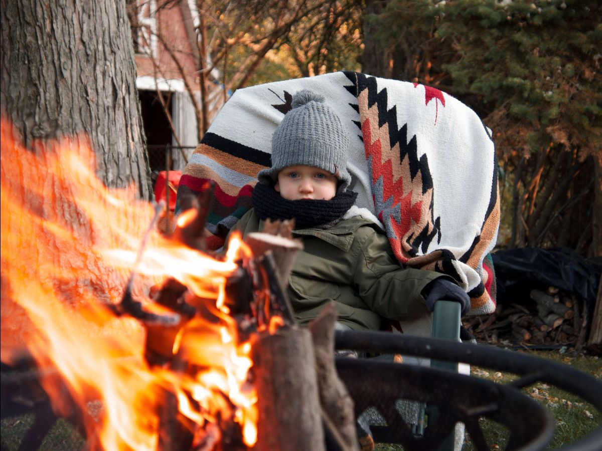 Small boy sits in chair in front of fire- ways to make leaf raking fun