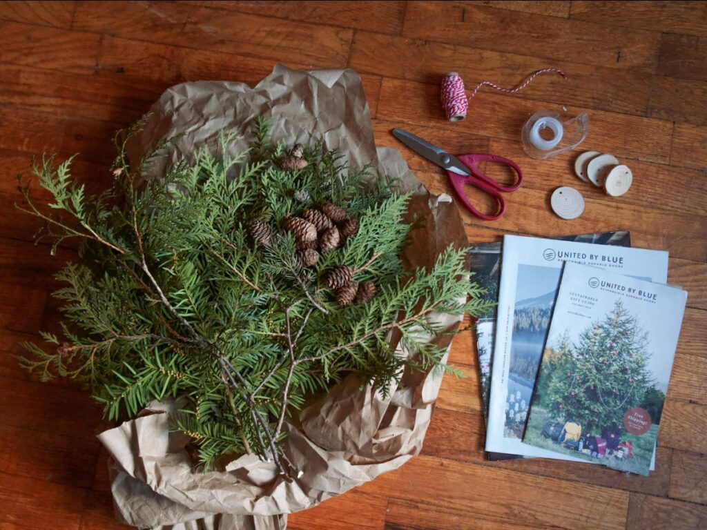 Collection of brown paper, evergreen, pine cones, scissors, string, etc. for making your own nature gift wrap