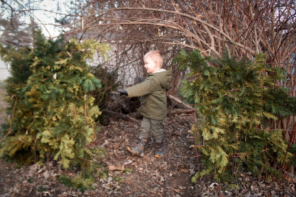 Small boy playing in fort outside: outdoor winter activities that don't require snow