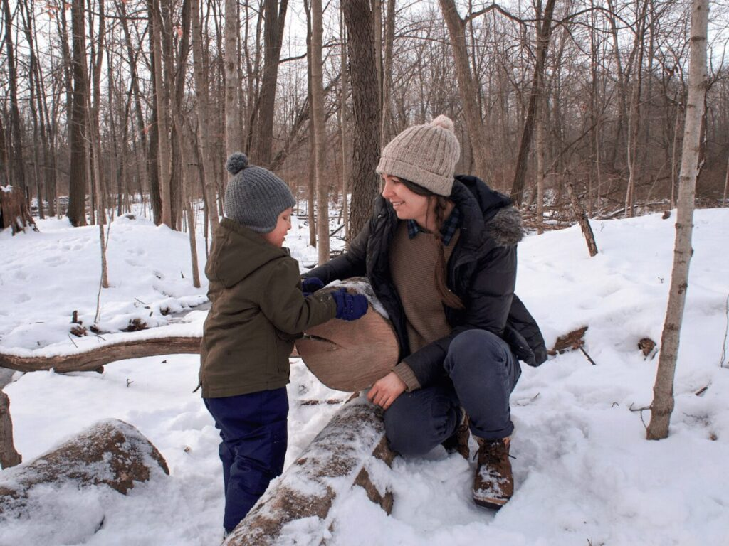 Little boy and his mom in snowy woods looking at tree stump together and counting tree rings