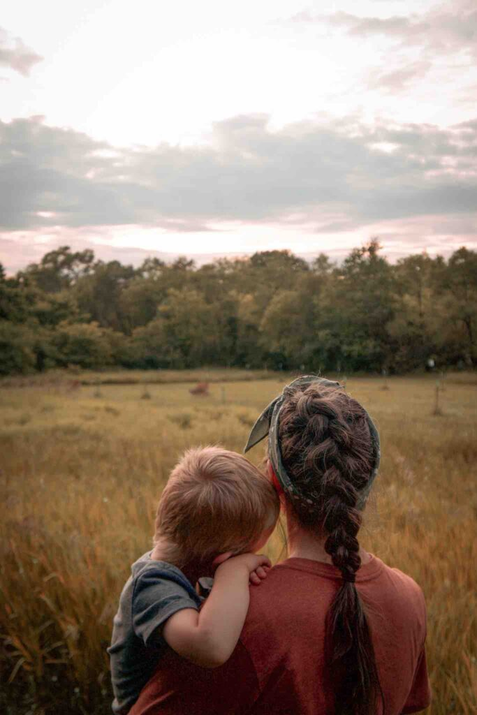 While hiking with toddler, mom is holding boy who rests head on her shoulder while looking out at deer in field.