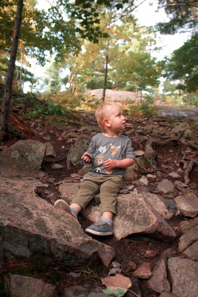 While hiking with toddler, small boy stops to sit on some large rocks in middle of trail.