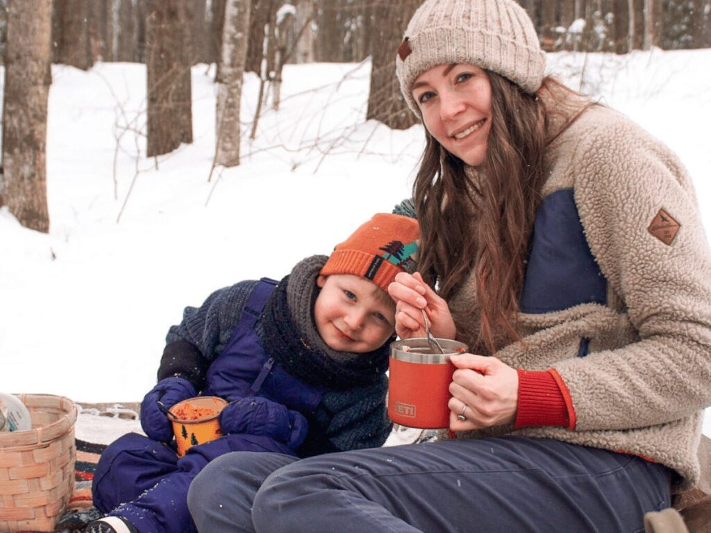 Mom and small boy sitting on blanket in snow during winter picnic eating soup in their mugs.