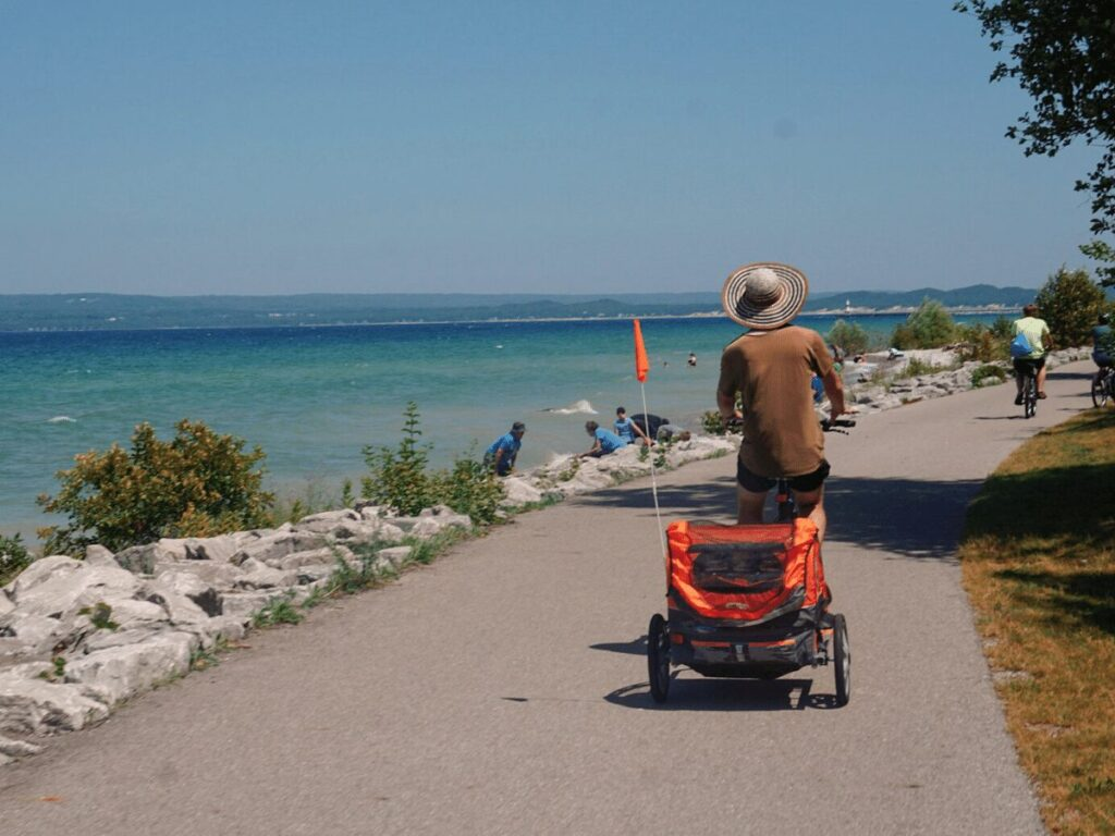 Father biking on path next to Lake Michigan pulling kid's trailer- family friendly outdoor activities to do in Petoskey, Michigan