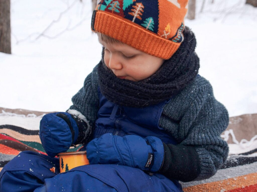 Little boy eating soup in a mug outside during winter picnic on blanket surrounded by snow