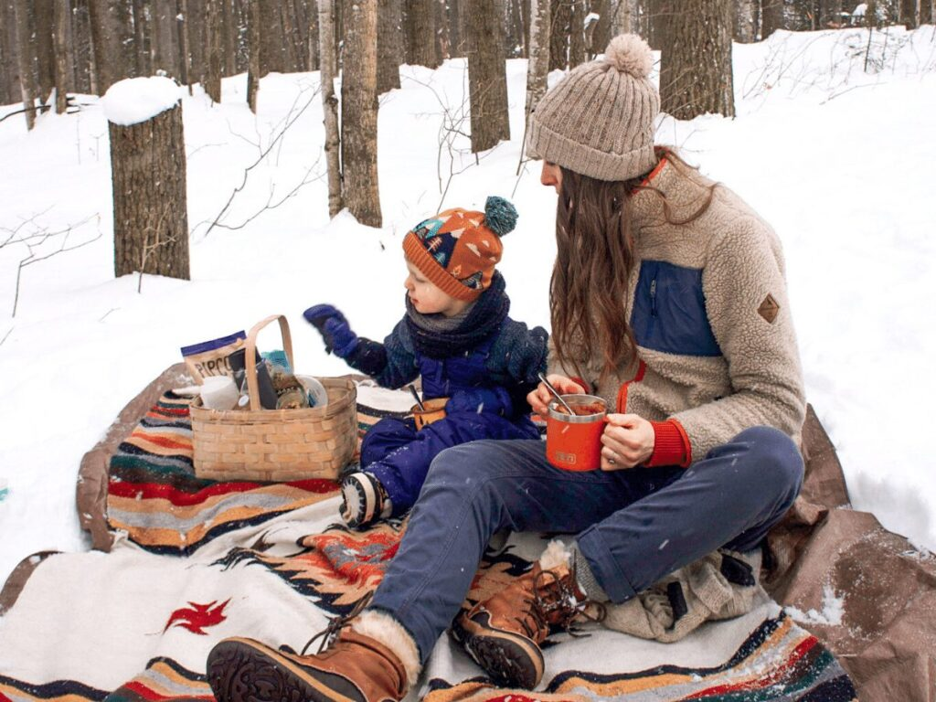 Mom and boy having picnic in winter on blanket in the snow