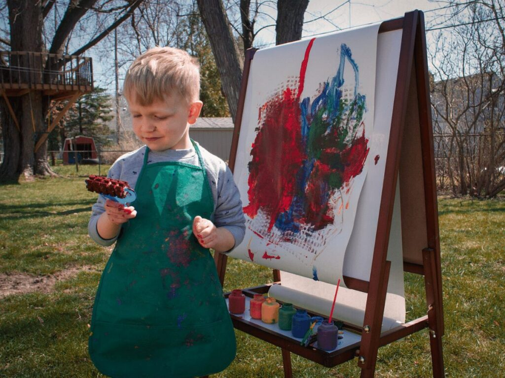 Outdoor creative arts ideas for kids: small boy painting on an easel in his backyard.