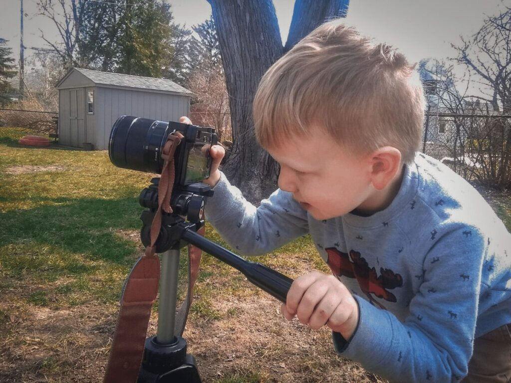 Outdoor Creative arts ideas for kids: Small boy with camera on tripod taking pictures in his backyard.