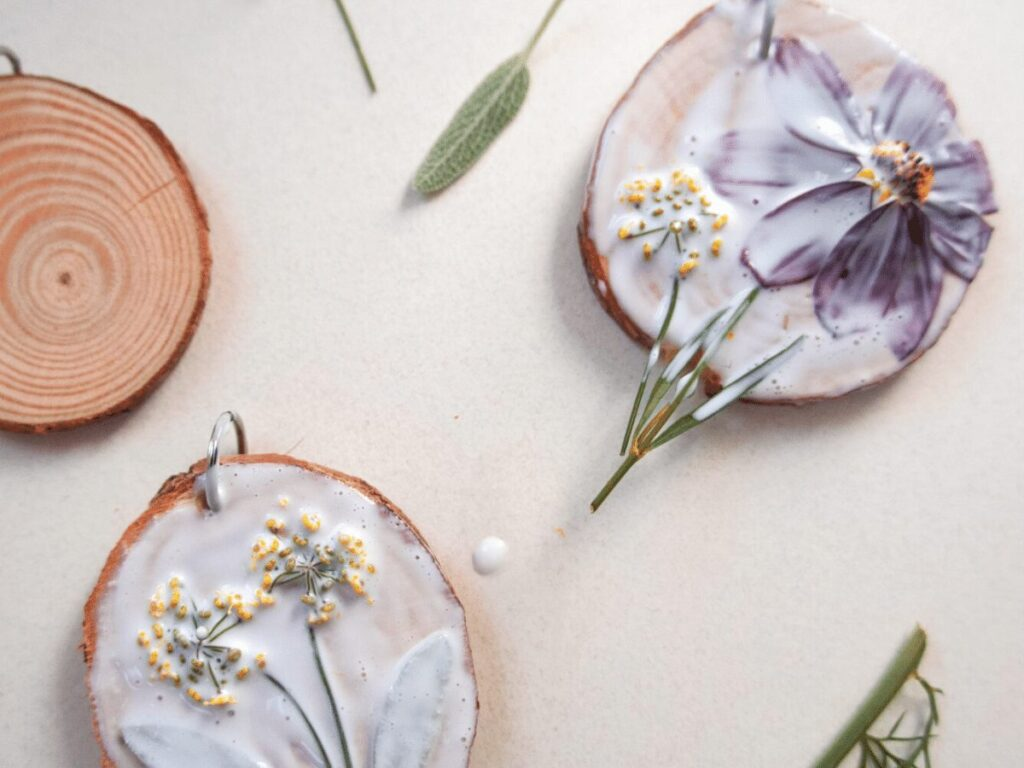 nature craft: small wood slices with flowers laid on top and glue painted over them.