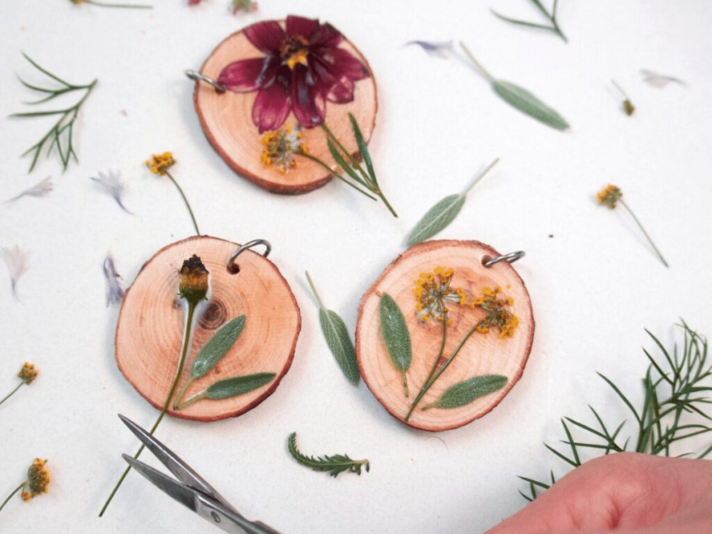 nature craft: small wood slices with pressed flowers for necklace-making.