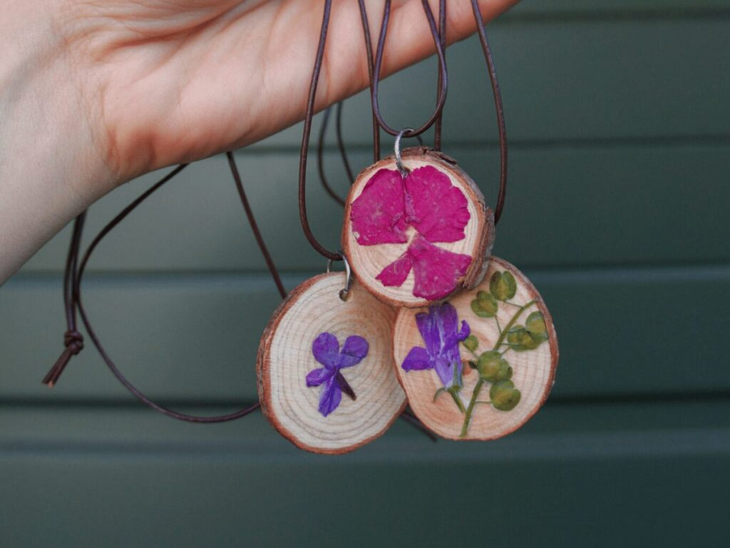 nature craft: finished wood slice necklaces with pressed flowers on leather cord.