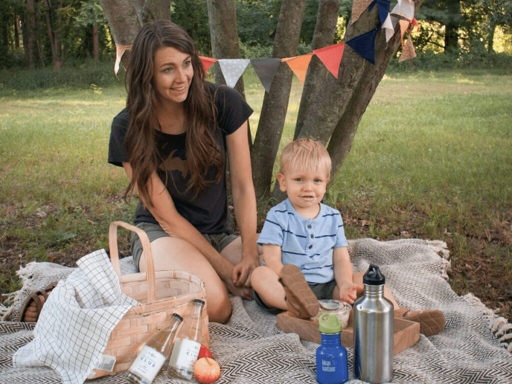 Mom and small boy sitting on picnic blanket with basket- summer bucket list