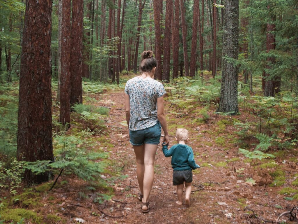 Mom and small boy walking on path in woods- summer bucket list