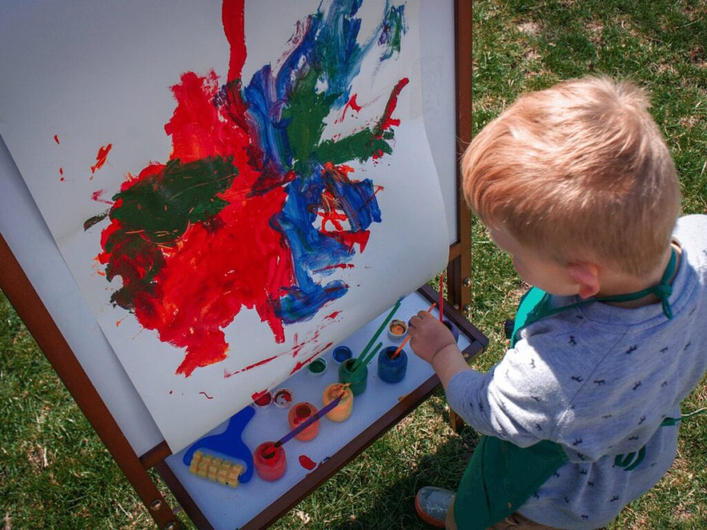 small boy painting picture on an easel out in the yard- summer bucket list