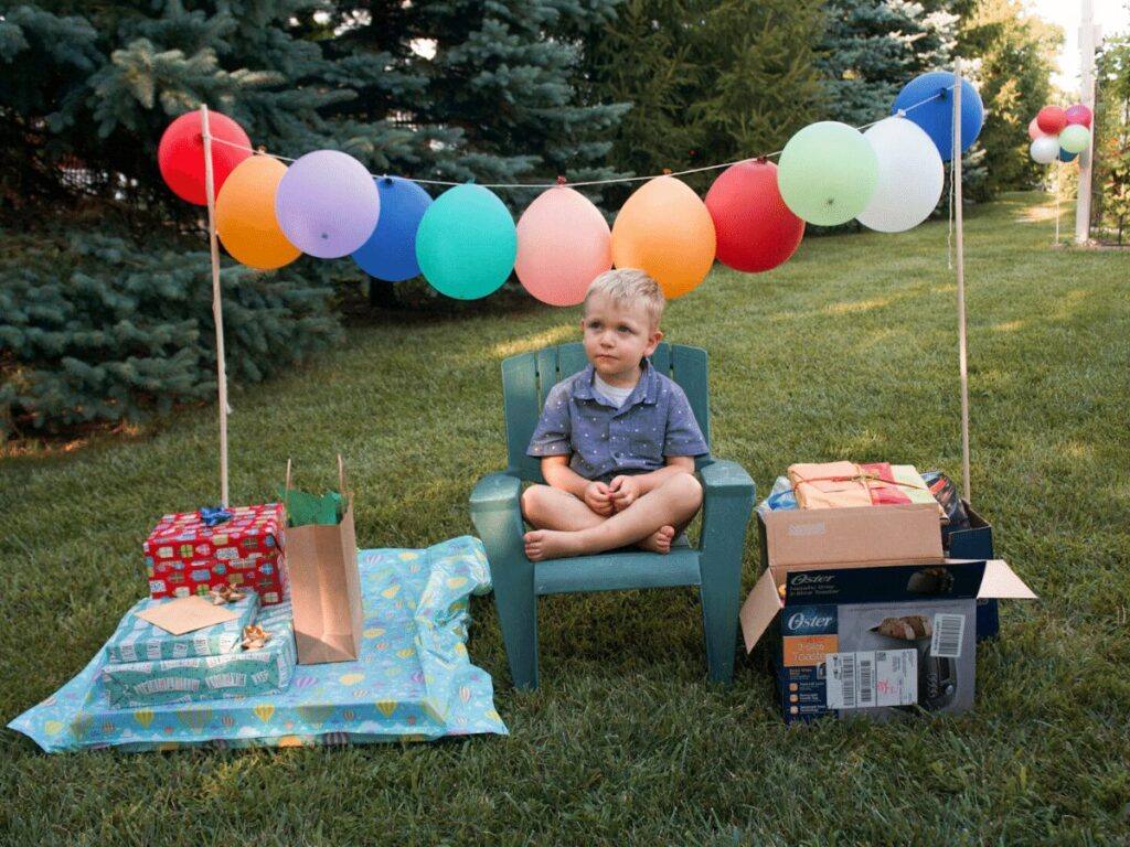 small boy sits on chair outside surrounded by balloons and presents- summer bucket list