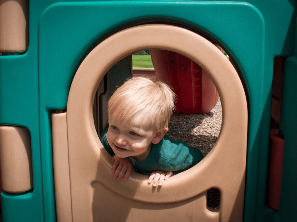 small boy peeks out window of playhouse- best outdoor toys