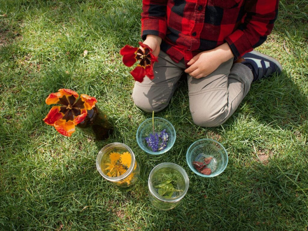 Small boy surrounded by jars  of different colored nature pieces for rainbow craft.