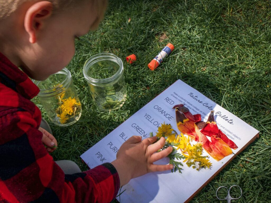 Small boy glues variety of colorful nature pieces onto paper for rainbow craft.