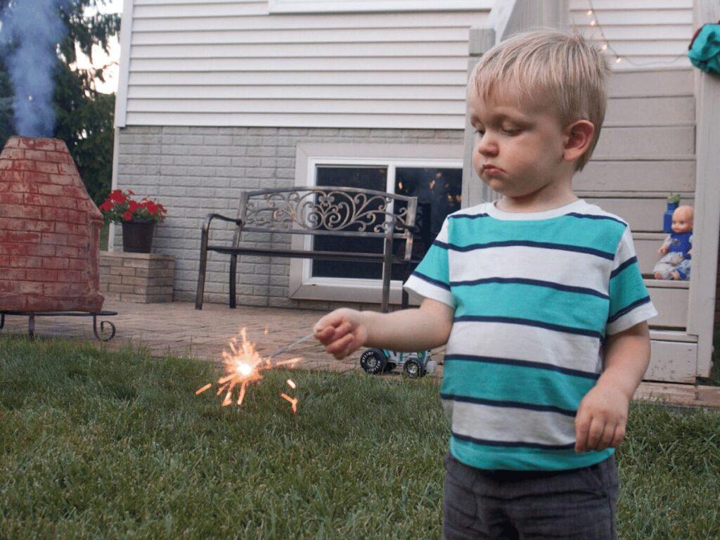small boy holding a sparkler- summer bucket list