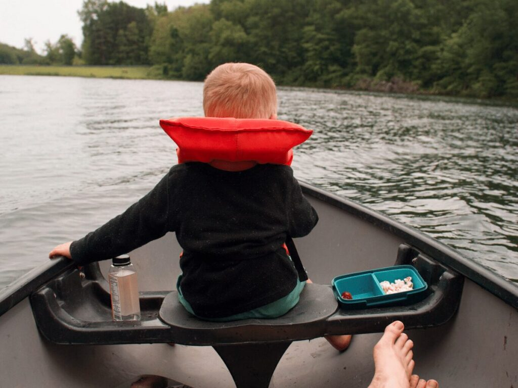 small boy sitting in front of a canoe- summer bucket list