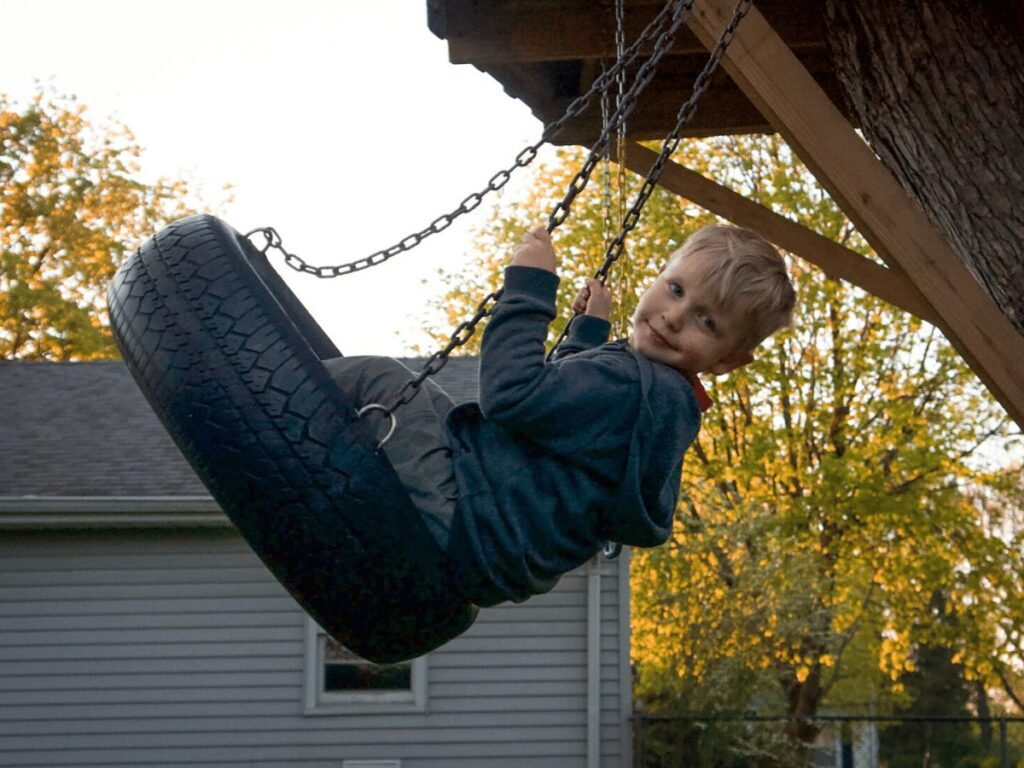 small boy in mid-air on tire swing- essential outdoor toys