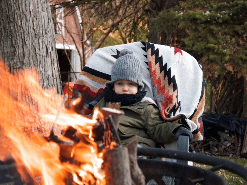 small boy sitting by fire- best outdoor toys