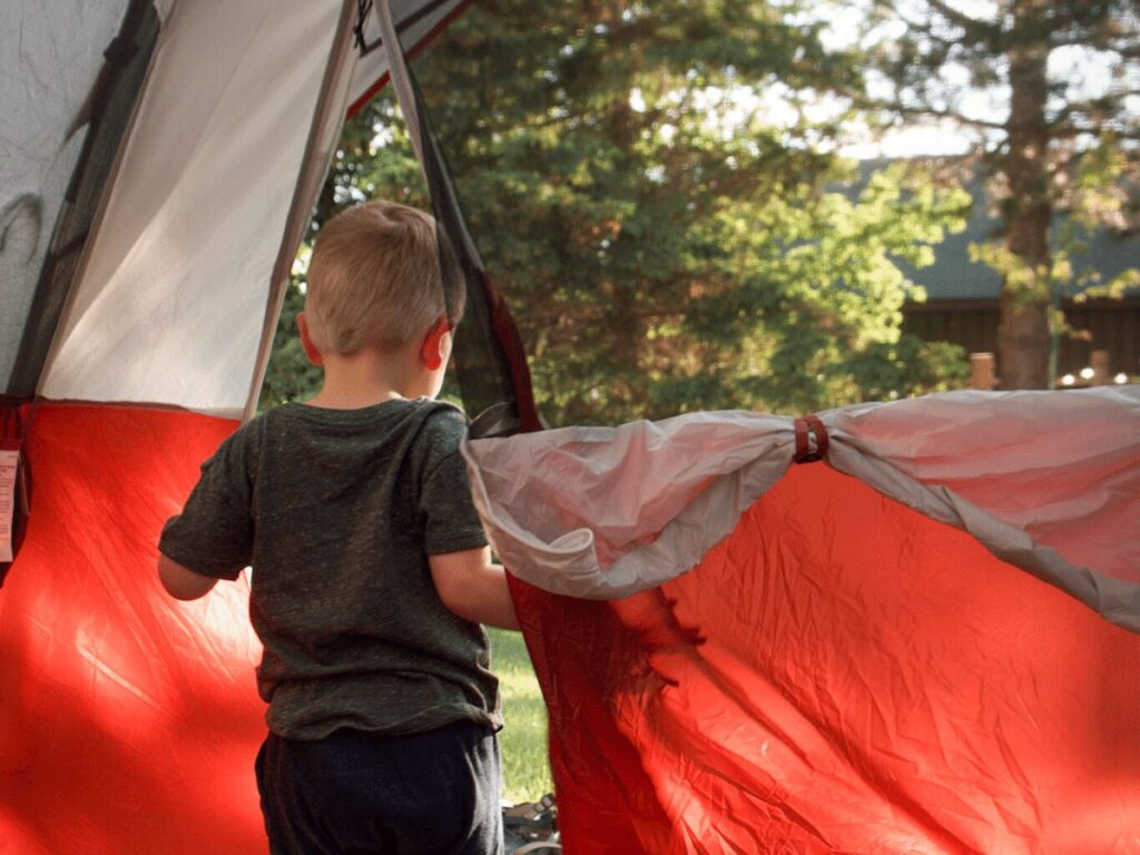 Summer bucket list- small boy opening doorway of tent while camping out