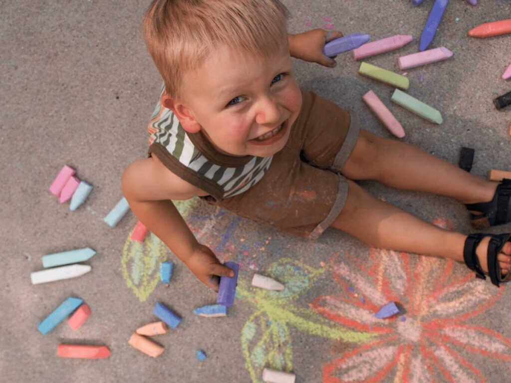 Small boy smiling up at camera while doing sidewalk chalk- summer bucket list