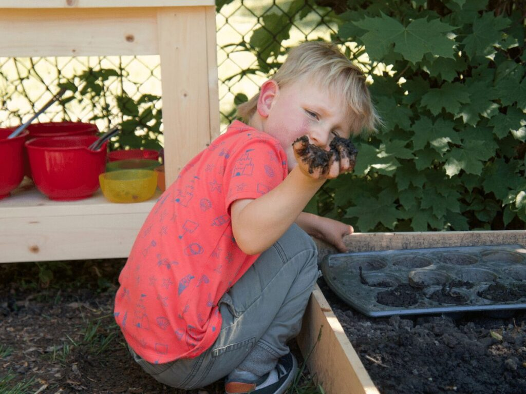small boy holds up mud in his hand while playing in mud kitchen