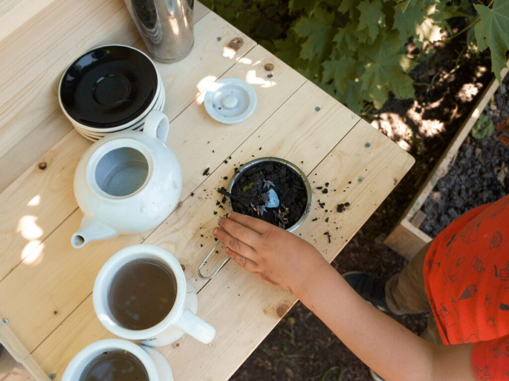 view from above of child's hand making mud pie on counter of mud kitchen