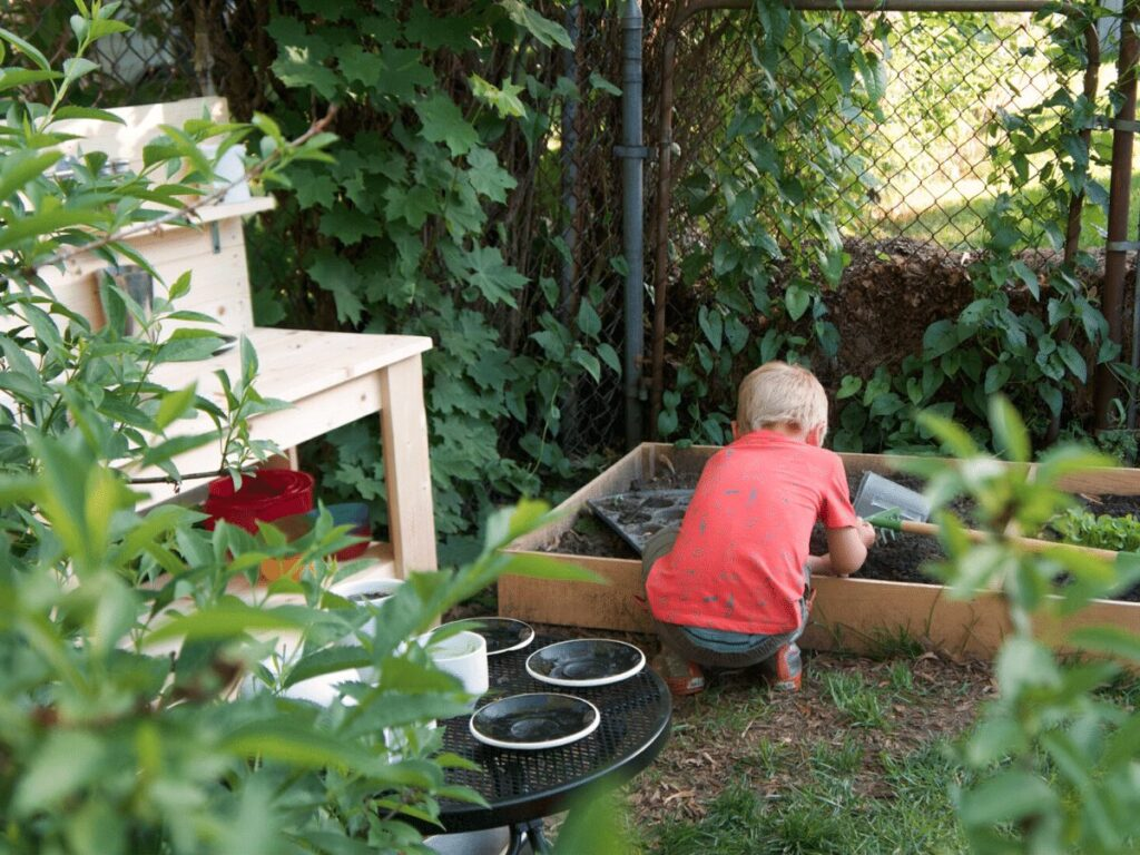 small boy plays in mud kitchen area outside