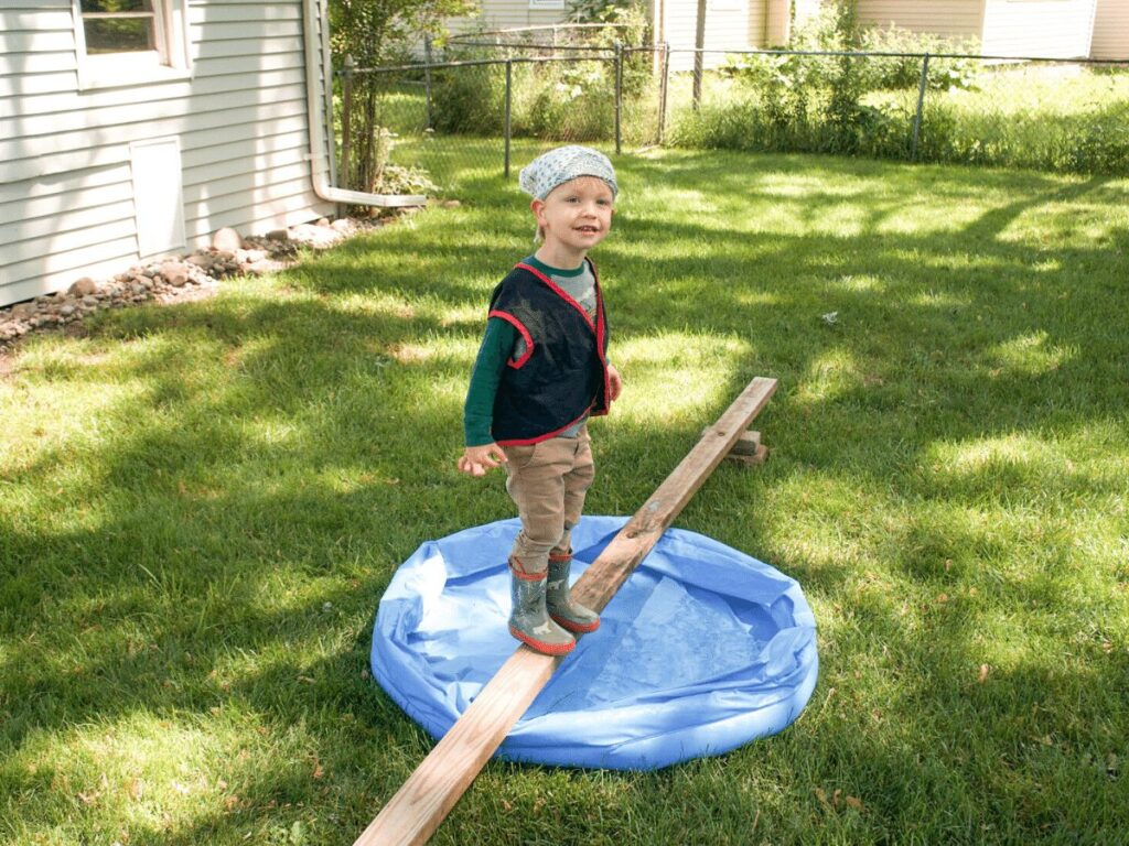 "small boy dressed as pirate walks ""plank"" over kiddie pool while on a treasure hunt"