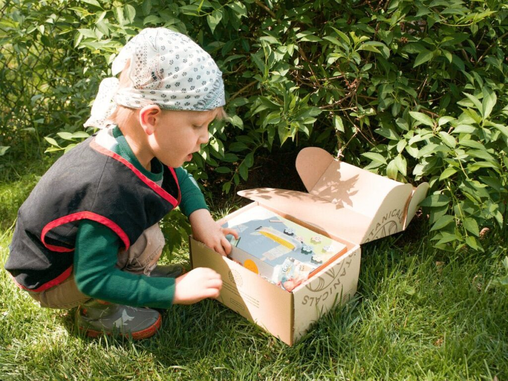 small boy opening up his shoe box treasure chest as part of treasure hunt