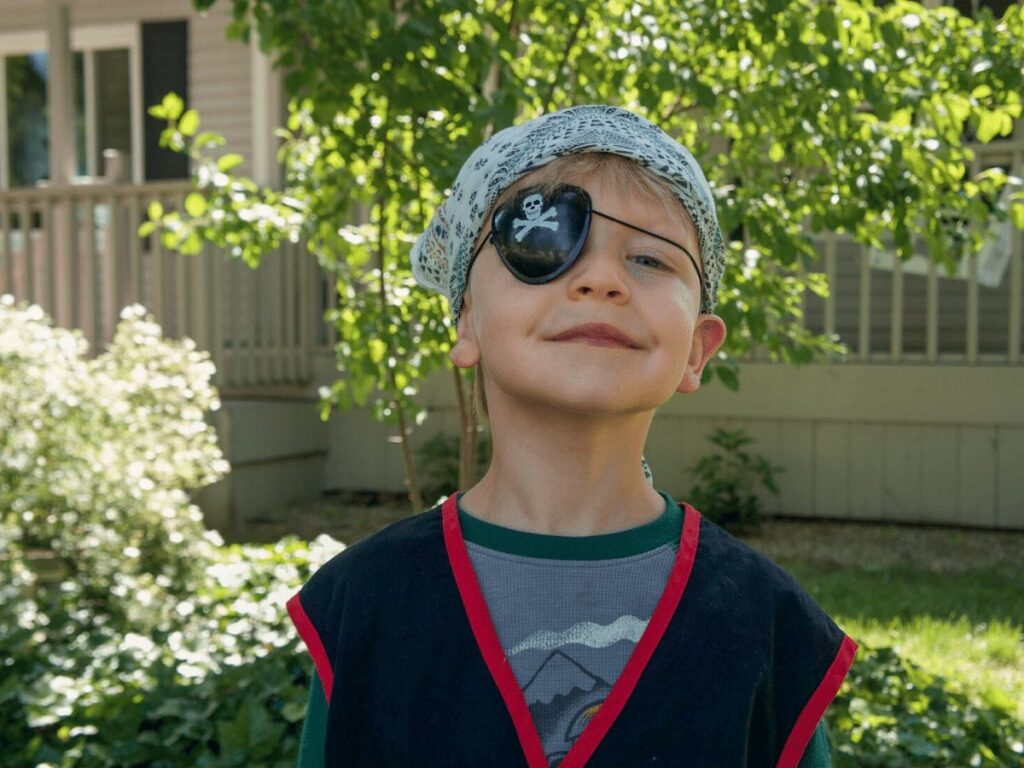 small boy smiles while dressed as pirate during treasure hunt