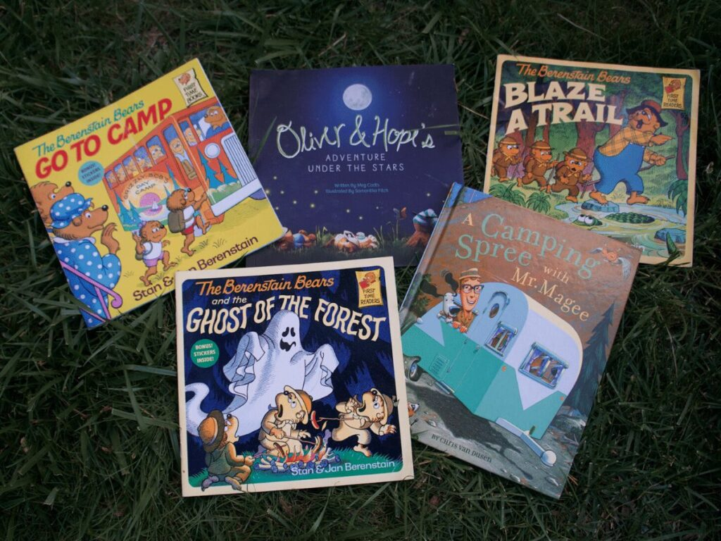 camp themed books spread out on grass to read by campfire