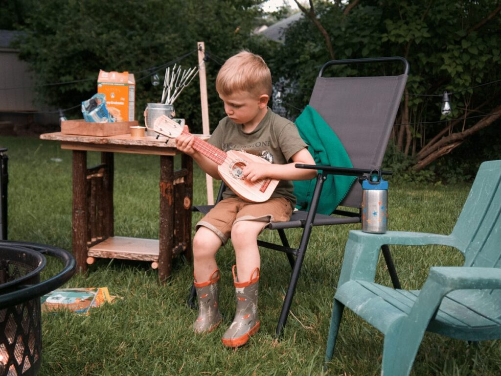 small boy strums guitar in front of campfire
