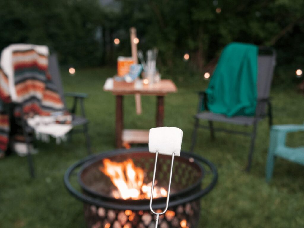 marshmallow in focus in front of a campfire with chairs, blankets, and twinkle lights in the backgrount.