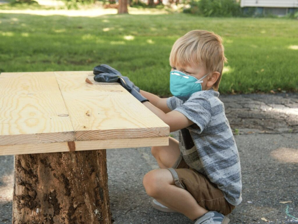 small boy wearing mask and gloves while sanding table top as part of furniture making business- business ideas for kids