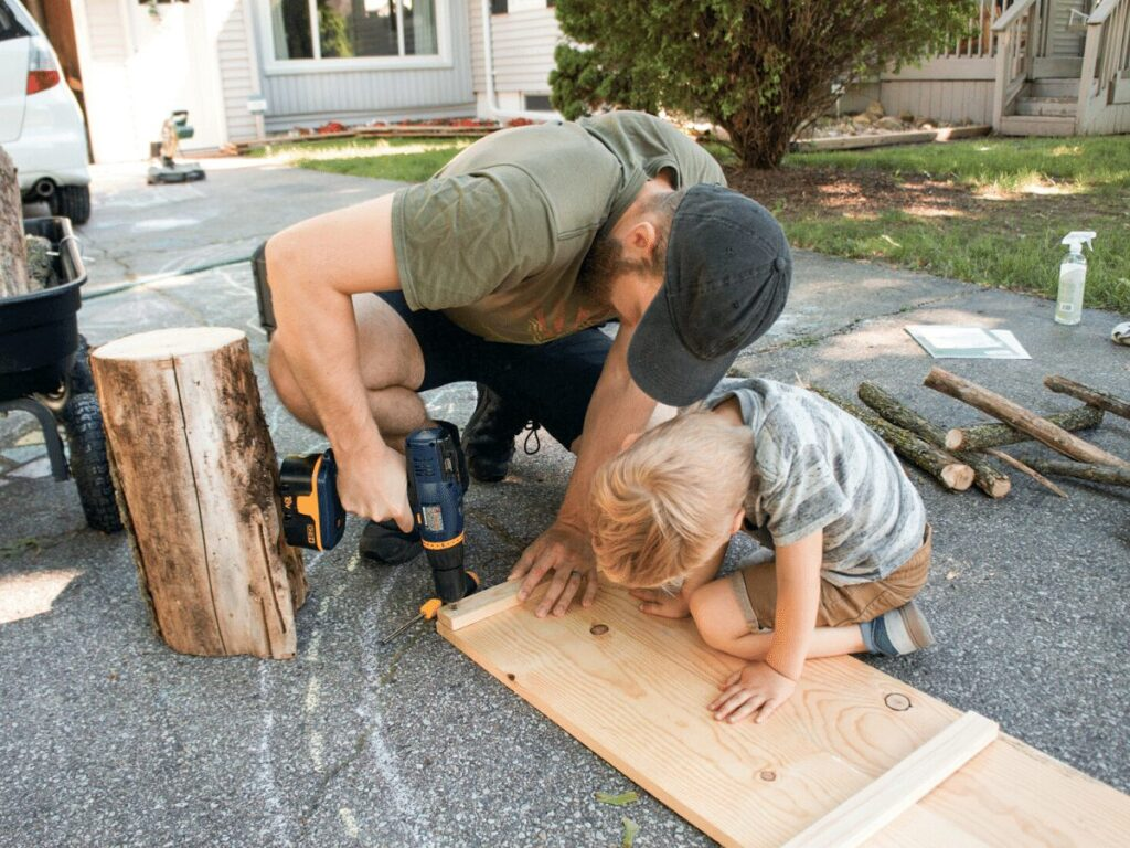 small boy helps dad with power drill while building table- business ideas for kids.