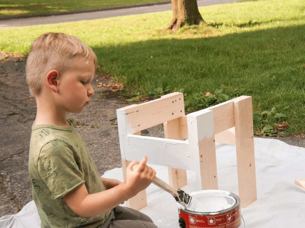 small boy paints table he's building- business ideas for kids