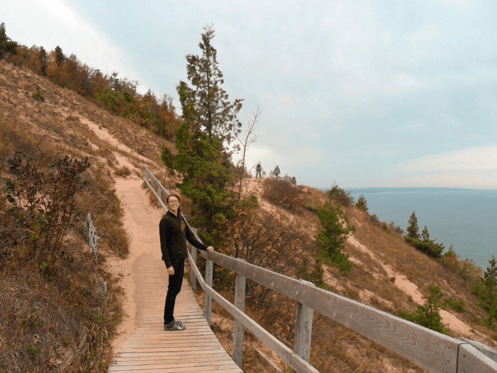 Girl standing on sandy boardwalk trail leading up side of dune- activities in traverse city