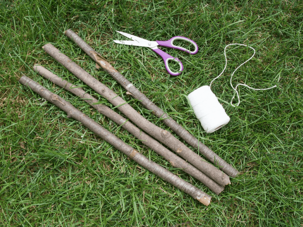materials needed for a nature weaving- four sticks, scissors, and a roll of string spread out on the grass