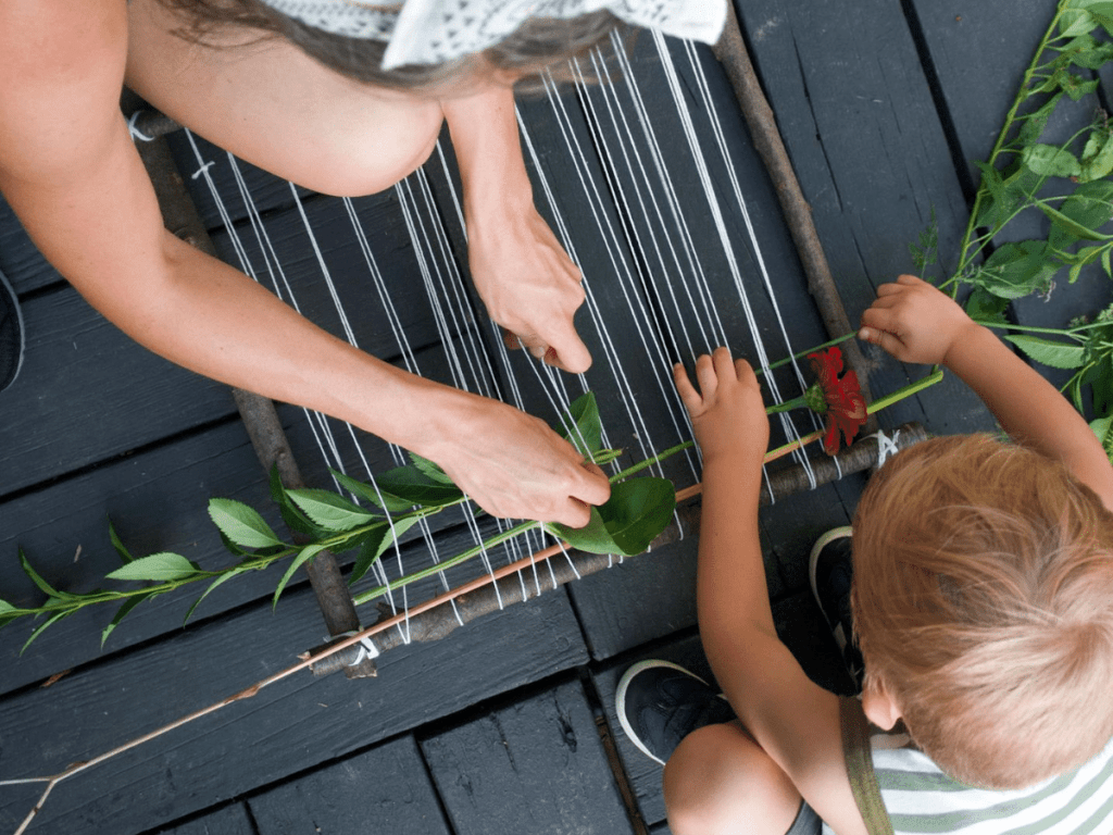 Overhead shot of mom and small boy weaving plants into loom to make a nature weaving