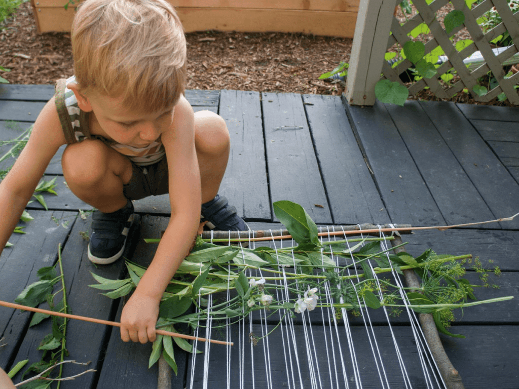 small boy adding more plants to his nature weaving loom