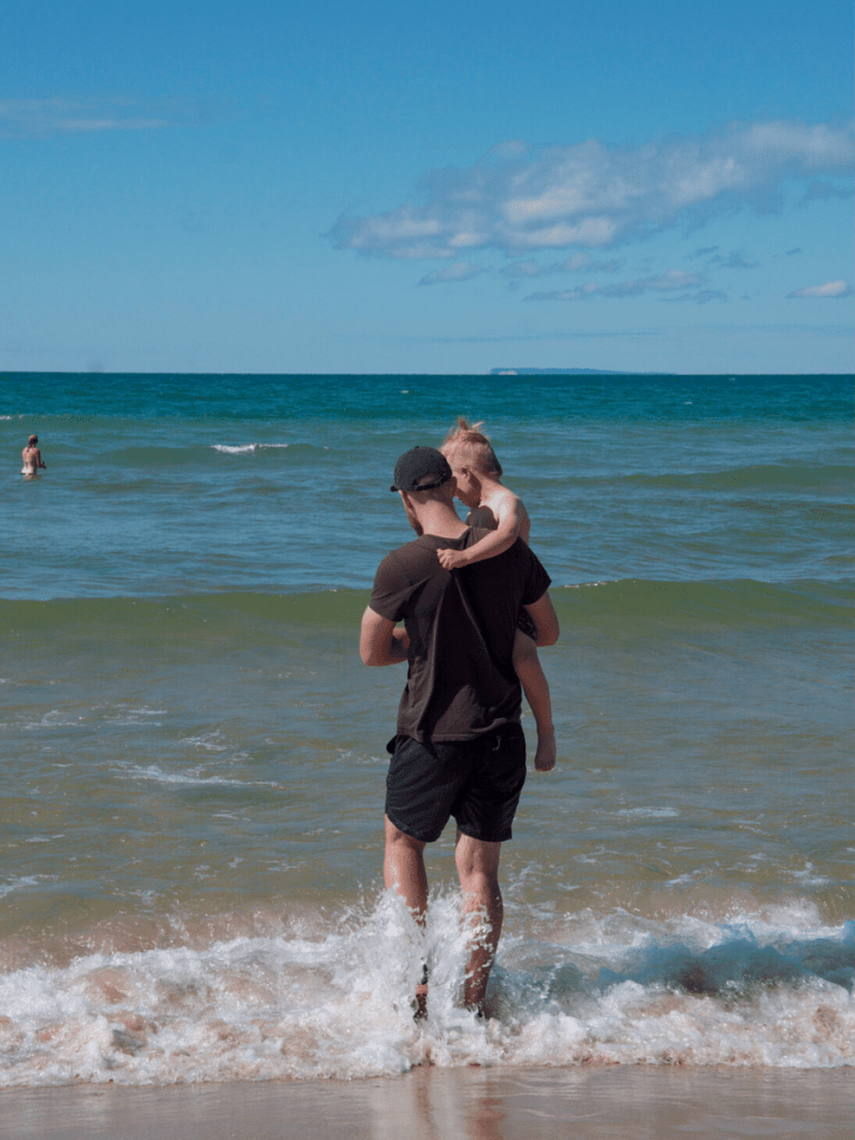 Dad holding small boy while walking out into turquoise water of lake michigan- activities in traverse city