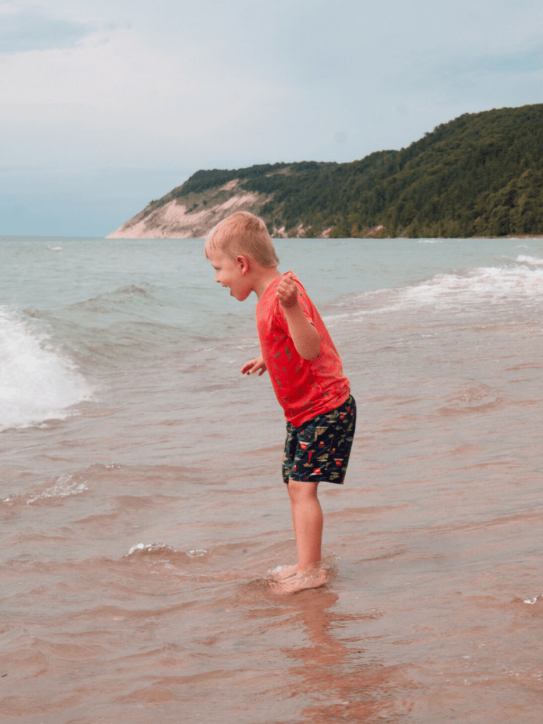 Small boy with look of glee on his face standing in water at edge of beach- activities in Traverse City