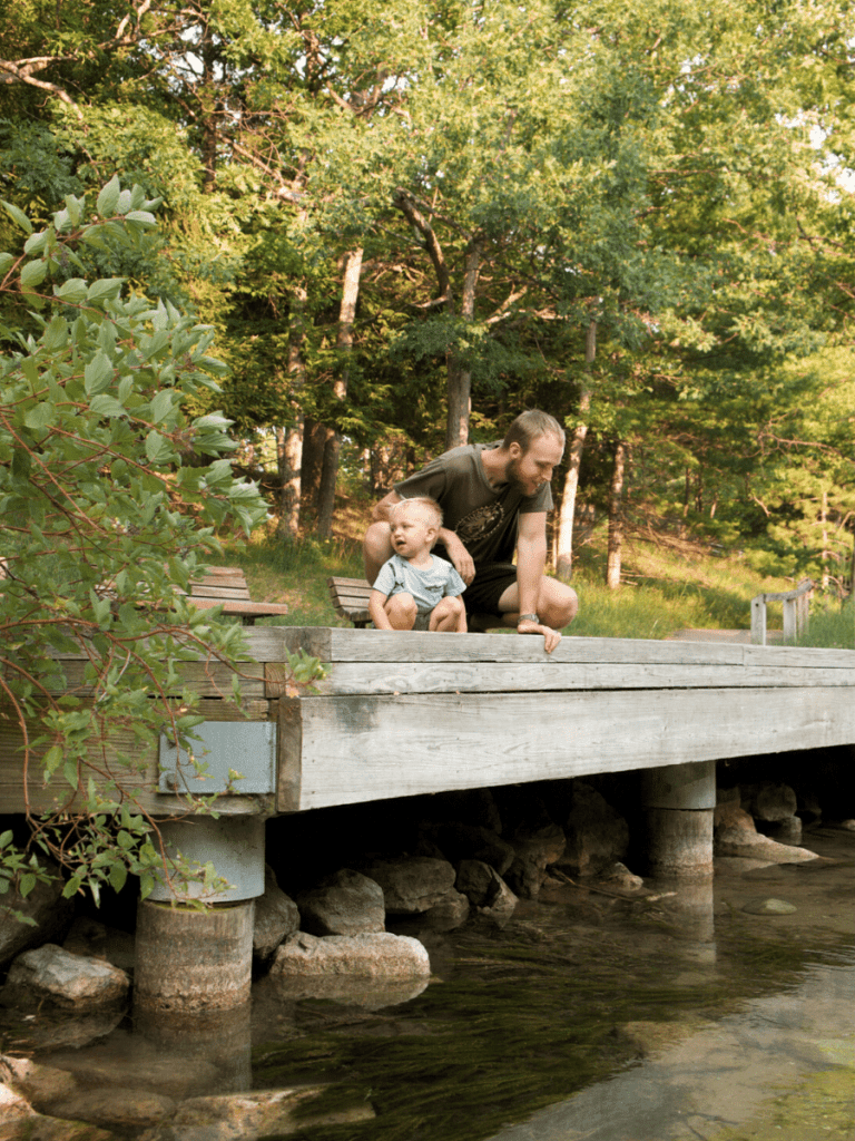 Dad and small boy sitting on dock above river- activities in traverse city