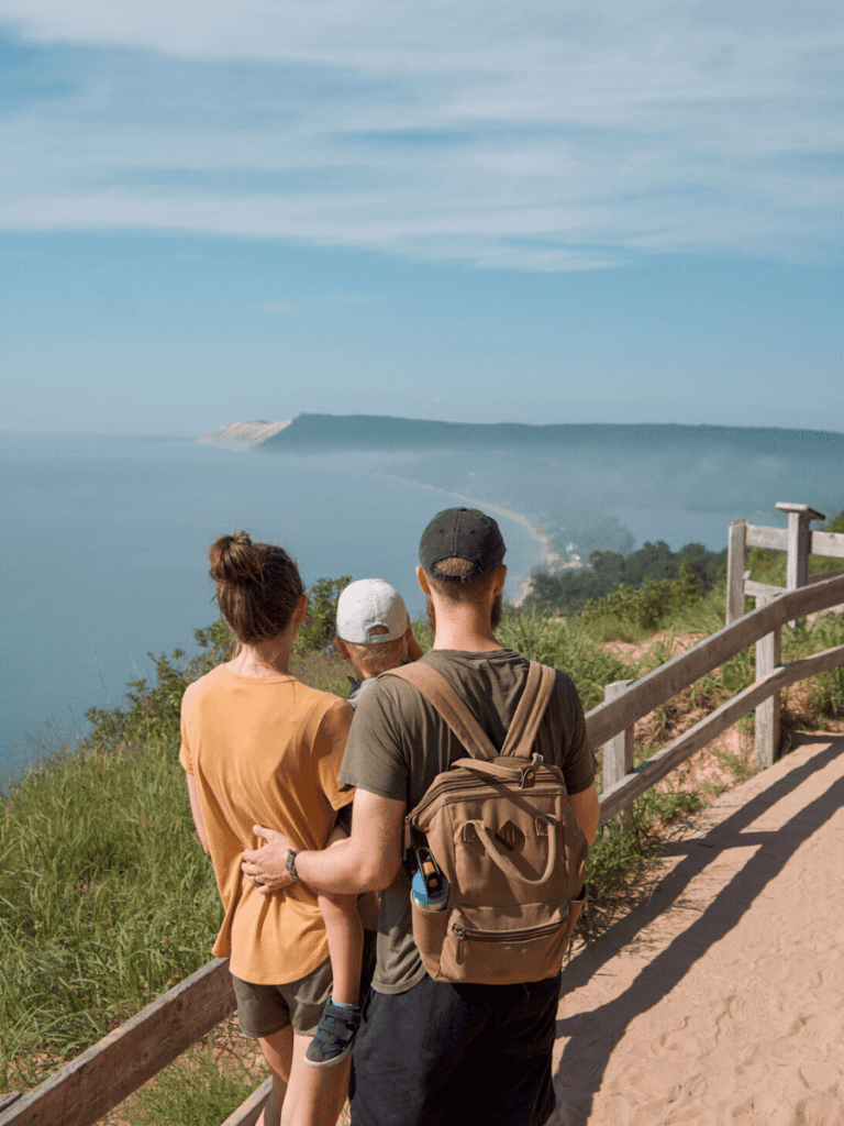 Family stands at top of cliff overlooking lake and bluffs in the distance- activities in traverse city