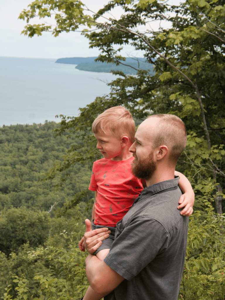Dad holds small boy at the top of cliff looking out over lake-activities in traverse city
