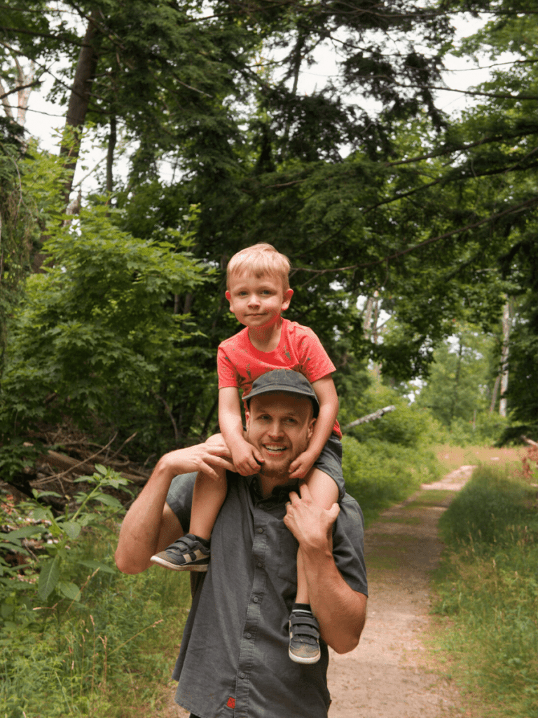 small boy rides on dad's shoulders while hiking down wooded path- activities in traverse city